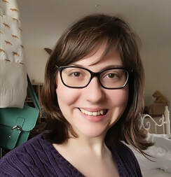 Amy is smiling into the camera, she has brown hair with a fringe and is wearing glasses.