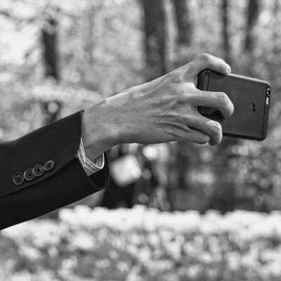 Extended arm with hand straining to hold a phone. Black and white image