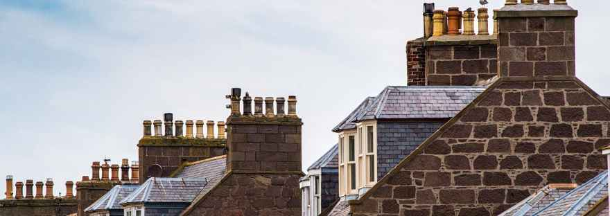 Chimneys and upstairs windows of brick terraced houses